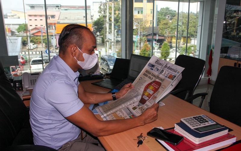 Kepala Cabang Toyota Samarinda Tatuk Hendrasmono saat membaca koran Bisnis Indonesia, di Graha Toyota Kota Samarinda, Kamis (10/6 - 2021).