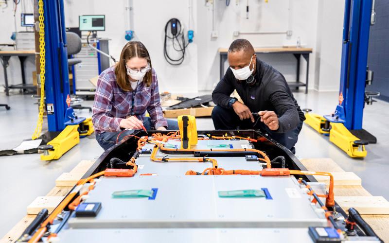 Dane Hardware, insinyur desain dan rilis Ford Motor Co.; dan Mary Fredrick, insinyur validasi baterai Ford Motor Co., mengukur voltase baterai menggunakan multi-meter digital di Laboratorium Uji dan Tolok Ukur Baterai Ford di Allen Park, Michigan.  - Ford Motor
