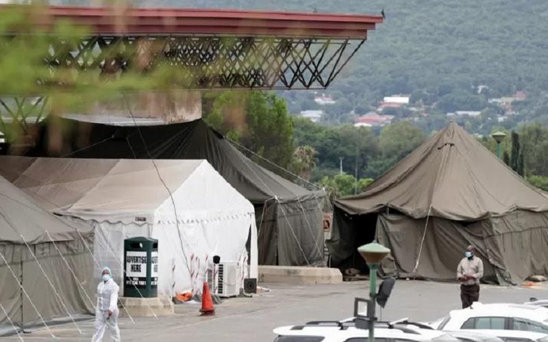 Petugas kesehatan berjalan melewati sejumlah tenda yang dipasang di lapangan parkir Rumah Sakit Akademi Steve Biko di Pretoria, Afrika Selatan, Senin (11/1/2021), di tengah penguncian nasional akibat wabah Covid-19. - Antara/Reuters\r\n