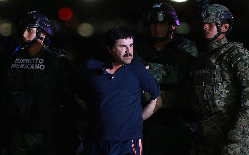 Joaquin Guzman alias El Chapo, gembong narkoba paling dicari di seluruh dunia, dikawal oleh aparat keamanan Meksiko di Mexico City, Meksiko, Jumat (8/1/2016). - Bloomberg/Susana Gonzalez