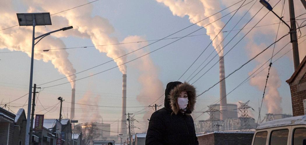 Asap mengepul saat seorang wanita mengenakan masker di dekat pembangkit listrik tenaga batu bara di Shanxi, China. Kevin Frayer / Getty Images  -  Bloomberg