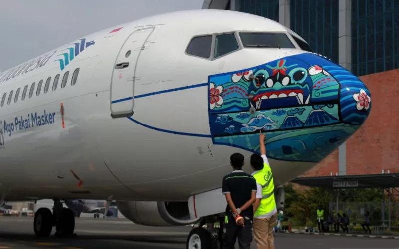 Pekerja melakukan pengecekan akhir livery masker pesawat yang terpilih sebagai pemenang, sebelum peluncuran pesawat Garuda Indonesia Boing 737-800 NG bercorak khusus yang menampilkan visual masker bertema