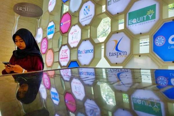 Pengunjung beraktivitas di dekat logo asuransi jiwa di gedung Asosiasi Asuransi Jiwa Indonesia (AAJI), Jakarta, Rabu (9/1/2019). - Bisnis/Felix Jody Kinarwan