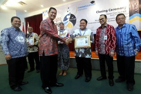 Pemimpin Action Coach Indonesia Prijono Arto Nugroho (ketiga kiri) disaksikan Direktur Mikro  PT Bank Pembangunan Daerah Jawa Barat dan Banten, Tbk. (Bank BJB) Agus Gunawan (kedua kanan), Kepala Dinas Koperasi dan UMKM Provinsi Jawa Barat Dudi Sudrajat Abdurachim (kanan) dan Pemimpin Divisi Kredit UMKM Bank BJB Arief Setyahadi (kiri) menyerahkan sertifikat kepada para peserta terbaik Program Jawara UMKM 2017 pada acara penutupannya di Bandung, Jawa Barat, Kamis (5/10). Bank BJB menyelenggakan program tersebut untuk mendukung tumbuh kembangnya UMKM di Jawa Barat dan Banten. Program direalisasikan dalam bentuk intensif Business Coaching yang diperuntukan bagi pengusaha UMKM.  JIBI/Bisnis/Rachman