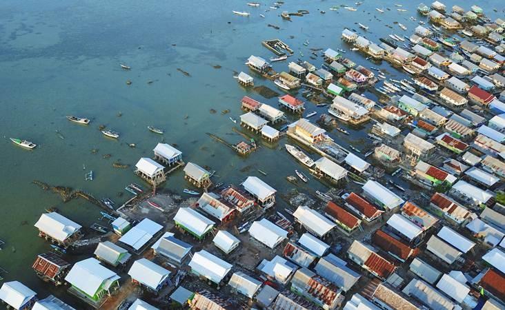 Foto udara permukiman padat warga di Pulau Bungin, Kecamatan Alas, Sumbawa Besar, Kabupaten Sumbawa, NTB, Selasa (9/4/2019). Pulau Bungin seluas 8,5 hektare tersebut merupakan salah satu pulau terpadat di dunia yang sebagian besar dihuni oleh Suku Bajo. Rumah-rumah di pulau tersebut dibangun di atas gundukan pasir dan karang yang saling berdempetan dan nyaris tidak ada ruang yang tersisa. ANTARA FOTO/Ahmad Subaidi