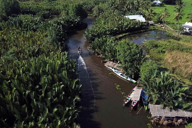 Wisatawan naik perahu melintasi sungai Pute, di Kabupaten Maros, Sulawesi Selatan, Sabtu (22/6). Sungai Pute dengan gugusan bukit-bukit kars menjadi daya tarik tersendiri bagi wisatawan. Bisnis/Paulus Tandi Bone