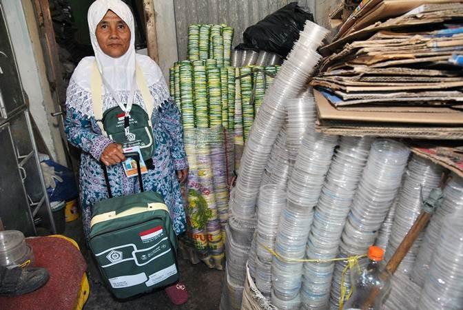 Pemulung Maryani (64 tahun) dengan koper hajinya diantara bekas minuman kemasan plastik yang dikumpulkannya untuk dijual di Kampung Pulo Geulis RT 02/04, Kelurahan Babakan Pasar, Kota Bogor, Jawa Barat, Jum'at (12/7/2019). Penghasilannya yang dikumpulkan dan ditabung selama 26 tahun dari hasil memulung barang bekas tersebut mengantarkan niatnya menunaikan ibadah haji ke tanah suci Mekkah bersama rombongan Jemaah Calon Haji (JCH) Kota Bogor Kloter 88. ANTARA FOTO/Arif Firmansyah
