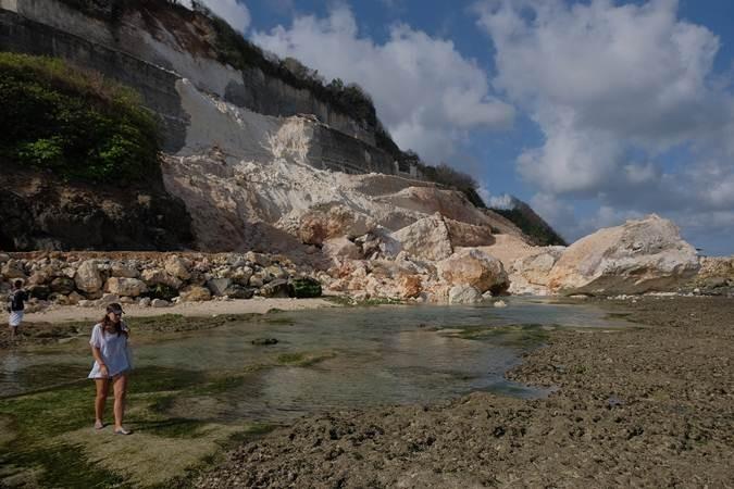 Wisatawan melintas di dekat reruntuhan tebing akibat gempa bumi di kawasan objek wisata Pantai Melasti, Badung, Bali, Selasa (16/7/2019). BPBD Bali mendata lima orang luka-luka akibat gempa berkekuatan 5,8 skala richter itu dan masih terus melakukan pendataan kerusakan akibat gempa secara keseluruhan di Bali. ANTARA FOTO/Nyoman Hendra Wibowo