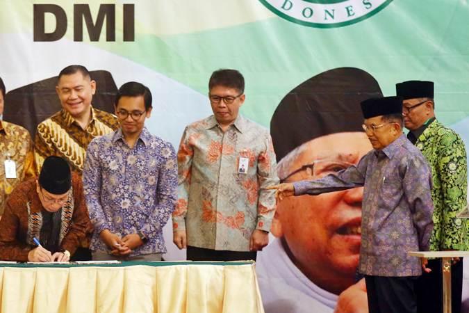 Wakil Ketua Umum Dewan Masjid Indonesia (DMI) K.H Masdar F. Mas'udi (kiri) menandatangani nota kesepahaman disaksikan Ketua DMI Jusuf Kalla (kanan) dan Direktur Utama BNI Syariah Firman Wibowo (dari kedua kiri), CEO Go-Pay Aldi Haryopratomo dan Direktur Utama Bank Syariah Mandiri Toni EB Subari saat acara Milad DMI di Jakarta, Rabu (17/7/2019). Kerja sama tersebut bertujuan mendorong teknologi membuat budaya tanpa uang tunai terus meluas, sehingga infak, sedekah maupun zakat umat tidak terkendala. Bisnis/Abdullah Azzam