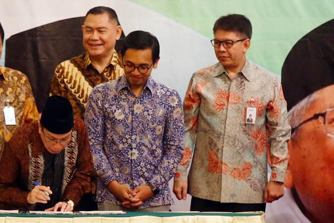 Wakil Ketua Umum Dewan Masjid Indonesia (DMI) K.H Masdar F. Mas'udi (dari kiri) menandatangani Nota Kesepahaman disaksikan Direktur Utama BNI Syariah Firman Wibowo, CEO Go-Pay Aldi Haryopratomo dan Direktur Utama Bank Syariah Mandiri Toni EB Subari saat acara Milad DMI di Jakarta, Rabu (17/7/2019). Kerja sama tersebut bertujuan mendorong teknologi membuat budaya tanpa uang tunai terus meluas, sehingga infak, sedekah maupun zakat umat tidak terkendala. Bisnis/Abdullah Azzam