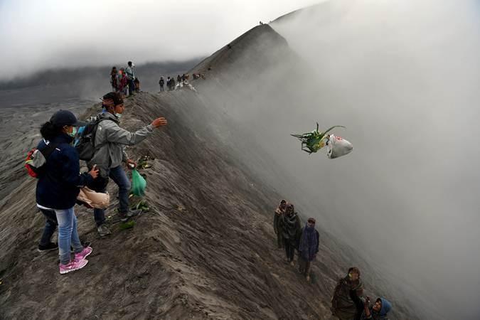 Warga suku Tengger melarung sesajen ke kawah Gunung Bromo pada Upacara Yadnya Kasada, Probolinggo, Jawa Timur, Kamis (18/7/2019). Upacara Kasada merupakan upacara adat masyarakat Suku Tengger sebagai bentuk ucapan syukur kepada Sang Hyang Widi sekaligus meminta berkah dan menjauhkan dari malapetaka. ANTARA FOTO/Zabur Karuru