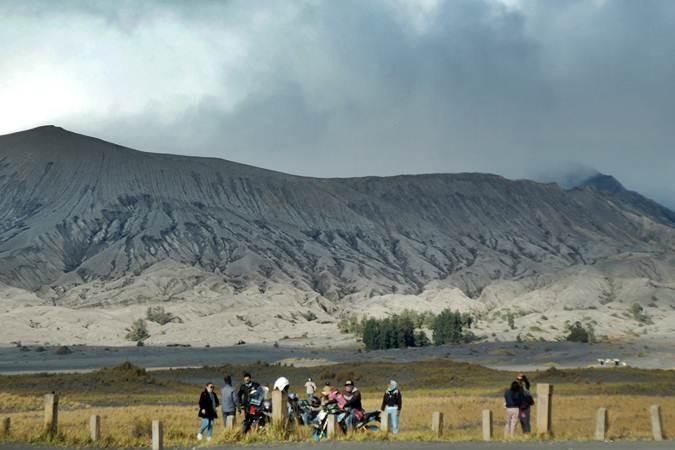 Wisatawan mengamati gunung Bromo yang mengalami erupsi dari kawasan lautan pasir di Probolinggo, Jawa Timur, Sabtu (20/7/2019). Pusat Vulkanologi Mitigasi Bencana Geologi (PVMBG) mengimbau masyarakat dan wisatawan tidak mendekat kawasan kawah Gunung Bromo sejauh radius satu kilometer. ANTARA FOTO/Vermensius Onggat Gebze