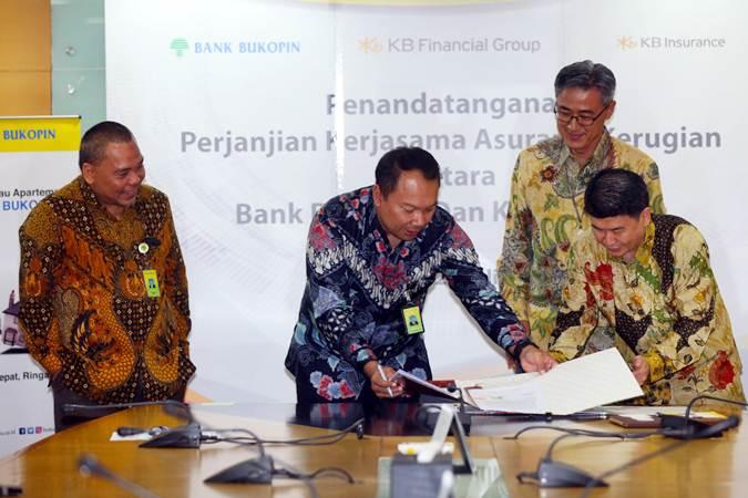 Direktur Konsumer PT Bank Bukopin Tbk. Rivan A Purwantono (kedua kiri) bertukar naskah perjanjian kerja sama dengan Direktur Operasional KB Insurance Hasan (kanan) disaksikan Direktur Utama Bank Bukopin Eko Rachmansyah Gindo (kiri) dan Presiden Direktur KB Insurance Cho Jeong Lae (kedua kanan) saat panandatanganan kerja sama di Jakarta, Selasa (23/7/2019). Kerja sama penjualan bancassurance referensi dalam rangka produk bank untuk asuransi kendaraan bermotor dan asuransi kebakaran itu bertujuan untuk memproteksi para debitur dengan jaminan perlindungan. Bisnis/Abdullah Azzam
