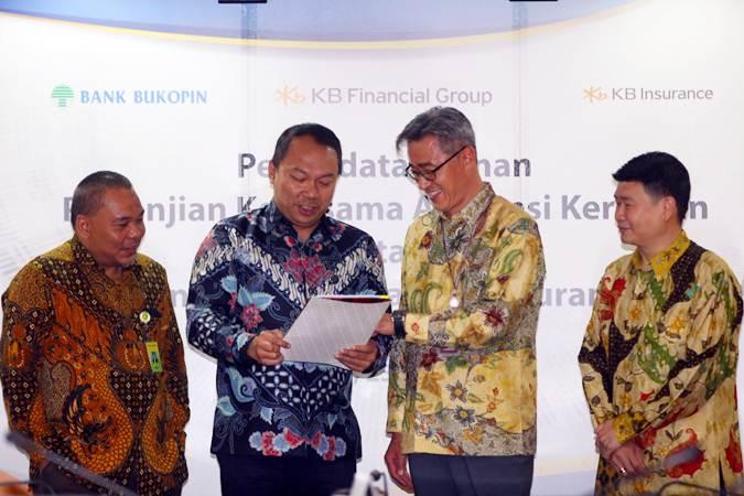 Direktur Konsumer PT Bank Bukopin Tbk. Rivan A Purwantono (kedua kiri) berbincang dengan Presiden Direktur KB Insurance Cho Jeong Lae (kedua kanan), Direktur Operasional KB Insurance Hasan (kanan) dan Direktur Utama Bank Bukopin Eko Rachmansyah Gindo (kiri) seusai panandatanganan kerja sama di Jakarta, Selasa (23/7/2019). Kerja sama penjualan bancassurance referensi dalam rangka produk bank untuk asuransi kendaraan bermotor dan asuransi kebakaran itu bertujuan untuk memproteksi para debitur dengan jaminan perlindungan. Bisnis/Abdullah Azzam