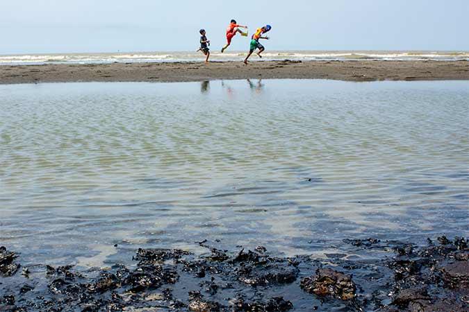 Anak-anak bermain di sekitar pantai terdampak tumpahan minyak mentah yang tercecer di Pesisir Pantai Tanjungsari, Karawang, Jawa Barat, Kamis (8/8). PT Pertamina mengklaim volume tumpahan minyak mentah yang tercecer akibat kebocoran gas di anjungan lepas pantai YY PHE ONWJ di wilayah Karawang tinggal 10 persen dibandingkan dari volume awal yang ditaksir mencapai 3.000 barel per hari. Antara/M Ibnu Chazar