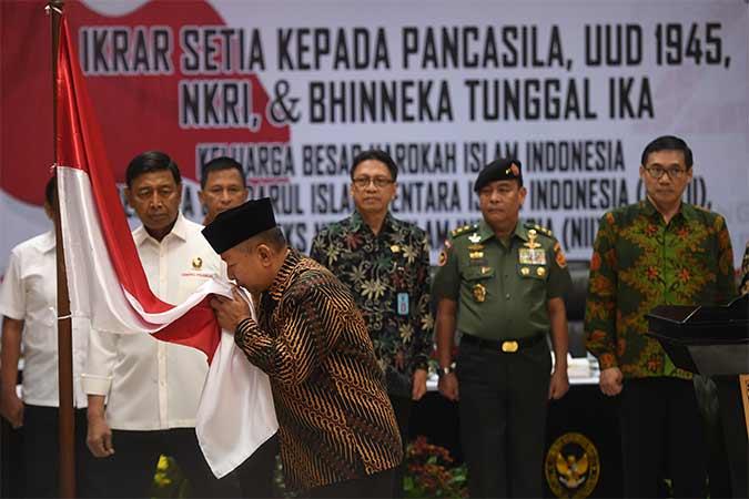 Menko Polhukam Wiranto (kiri) menyaksikan anak pemimpin Darul Islam/Tentara Islam Indonesia (DI/TII) Sekarmaji Marijan Kartosuwiryo, Sarjono Kartosuwiryo (kedua kiri) mencium bendera merah putih dalam acara pengucapan ikrar setia kepada Pancasila, UUD 45, NKRI dan Bhineka Tunggal Ika di Jakarta, Selasa (13/8). Sebanyak 14 orang Keluarga Besar Harokah Islam Indonesia, mantan anggota Darul Islam/Tentara Islam Indonesia (DI/TII) dan mantan anggota Negara Islam Indonesia (NII) mengikuti pembacaan ikrar setia tersebut. Antara/Akbar Nugroho Gumay