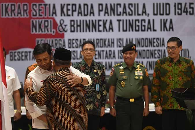 Menko Polhukam Wiranto (kiri) berpelukan dengan anak pemimpin Darul Islam/Tentara Islam Indonesia (DI/TII) Sekarmaji Marijan Kartosuwiryo, Sarjono Kartosuwiryo (kedua kiri) dalam acara pengucapan ikrar setia kepada Pancasila, UUD 45, NKRI dan Bhineka Tunggal Ika di Jakarta, Selasa (13/08/2019). Sebanyak 14 orang Keluarga Besar Harokah Islam Indonesia, mantan anggota Darul Islam/Tentara Islam Indonesia (DI/TII) dan mantan anggota Negara Islam Indonesia (NII) mengikuti pembacaan ikrar setia tersebut. Antara/Akbar Nugroho Gumay