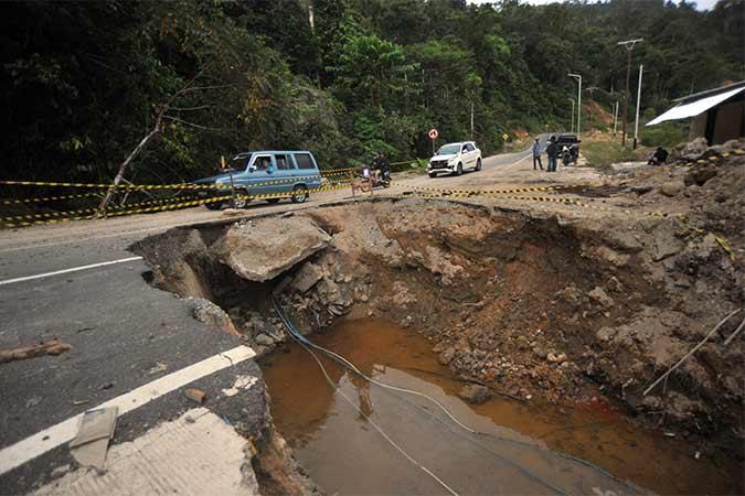Kendaraan melintas di bahu jalan yang amblas, di Nagari Sungai Nyalo Mudiak Aia, Kab.Pesisir Selatan, Sumatra Barat, Senin (12/8). Jalan nasional akses Kawasan Wisata Terpadu Mandeh yang baru selesai dibangun awal 2019 itu, amblas sejak Maret lalu dan belum diperbaiki, sehingga kendaraan terpaksa melintas di bahu jalan. Antara/Iggoy el Fitra