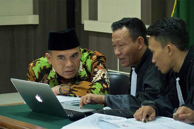 Terdakwa kasus suap terhadap hakim PN Semarang yang mengadili gugatan praperadilan tentang penetapan tersangka, Bupati nonaktif Jepara Ahmad Marzuqi (kiri), berdiskusi dengan penasehat hukumnya dalam sidang dengan agenda pembacaan tuntutan, di Pengadilan Tipikor Semarang, Jawa Tengah, Selasa (13/8). Jaksa Penuntut Umum dari KPK menuntut Ahmad Marzuqi dengan hukuman empat tahun penjara dan denda Rp500 juta subsider enam bulan kurungan serta pencabutan hak politiknya selama lima tahun. Antara/R. Rekotomo