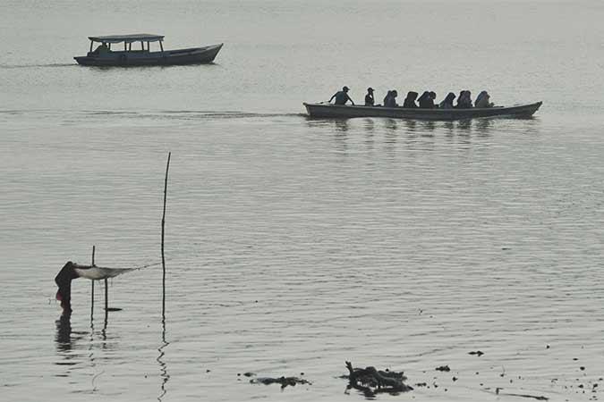 Penyedia jasa penyeberangan perahu membawa penumpang melintasi Sungai Batanghari yang diselimuti kabut asap tipis di Jambi, Rabu (14/8). Antara/Wahdi Septiawan
