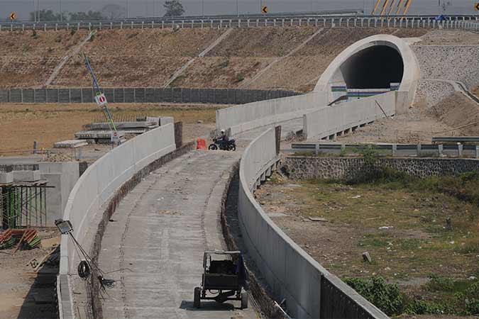 Pengendara motor melintasi area pembangunan jalur terowongan rel kereta api Bandara Adi Soemarmo di Ngemplak, Boyolali, Jawa Tengah, Rabu (14/8). Jalur kereta api yang menghubungkan Bandara Adi Soemarmo - Stasiun Balapan Solo sepanjang 13,5 km tersebut dibangun dengan jalur tunggal. Antara/Aloysius Jarot Nugroho
