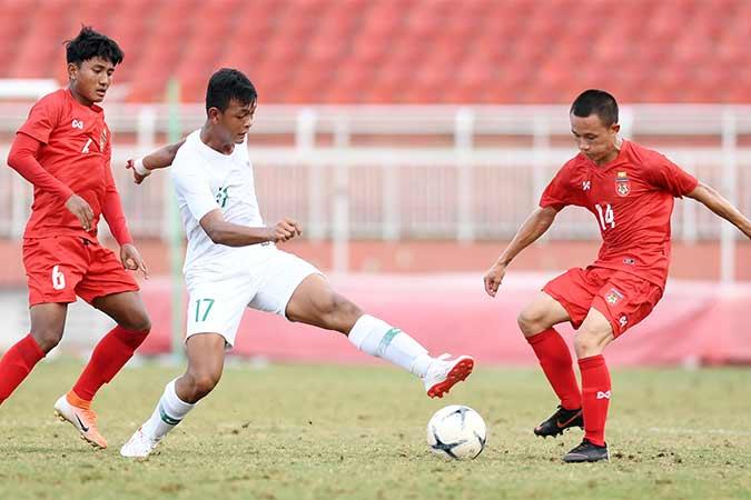 Pesepakbola Indonesia Saddam Emiruddin (tengah) berusaha melewati dua pesepakbola Myanmar Ye Min Kyew (kanan) dan Yan Kyaw Soe, saat bertanding pada penyisihan Grup A Piala AFF U-18 2019 di Stadion Thong Nhat, Ho Chi Minh, Vietnam, Rabu (14/8). Indonesia bermain imbang dengan Myanmar dengan skor 1-1 (0-0) dan menjadi juara Grup A dengan poin 13. Antara/Yusran Uccang