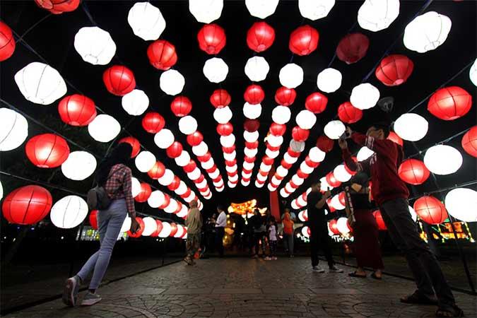 Pengunjung menikmati keindahan warna-warni lampu dalam Festival Of Light di kawasan Monumen Nasional (Monas), Jakarta, Rabu (14/8). Pertunjukkan tersebut diselenggarakan Dinas Pariwisata dan Kebudayaan DKI Jakarta sebagai rangkaian acara peringatan HUT ke-74 Republik Indonesia, dan berlangsung mulai 14-25 Agustus 2019. Bisnis/Arief Hermawan P.
