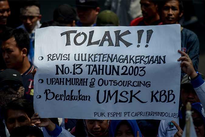 Massa aksi yang tergabung dari berbagai organisasi buruh melakukan aksi di halaman Gedung Sate, Bandung, Jawa Barat, Kamis (22/8). Dalam aksinya mereka menolak revisi UU no 13 Tahun 2003 terkait upah murah serta meminta pemerintah untuk memberlakukan UMSK. Antara/Raisan Al Farisi