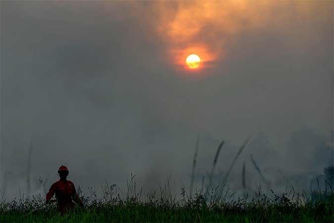 Petugas gabungan dari TNI, Polri, BPBD Provinsi Sumatra Selatan, BPBD Kabupaten Ogan Ilir dan Manggala Agni Daops Banyuasin berusaha memadamkan api yang membakar lahan di Desa Muara Baru Dua, Pemulutan, Ogan Ilir, Sumatra Selatan, Kamis (22/8). Berdasarkan pantauan satelit milik Lembaga Penerbangan dan Antariksa Nasional (LAPAN) terdapat 695 titik api yang terdeteksi di sejumlah wilayah yang ada di Indonesia. Antara/Mushaful Ima