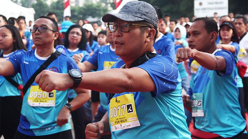 Direktur Utama PT Bursa Efek Indonesia Inarno Djajadi melakukan pemanasan sebelum mengikuti Fun Run 5K and Fun Walk 2.5K Pasar Modal di Jakarta, Minggu (25/8/2019). Acara ini merupakan rangkaian peringatan diaktifkannya kembali Pasar Modal yang diikuti ratusan peserta. Bisnis/Triawanda Tirta Aditya