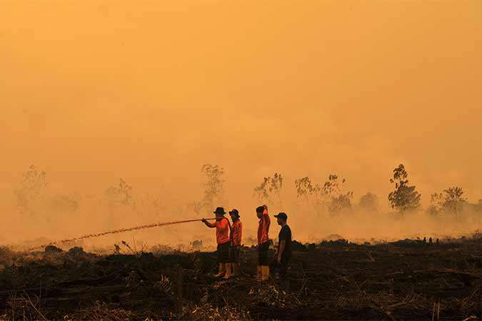 Petugas SAR Direktorat Sabhara Polda Jambi memadamkan kebakaran lahan gambut milik salah satu perusahaan di Puding, Kumpeh Ilir, Muarojambi, Jambi, Rabu (11/9). Asap kebakaran hutan dan lahan di Provinsi Jambi telah mengakibatkan aktivitas belajar mengajar di beberapa kota/kabupaten setempat terganggu dan terpaksa diliburkan, sementara upaya pemadaman masih terus dilakukan sejumlah pihak. Antara/Wahdi Septiawan