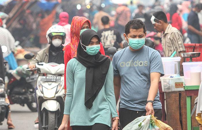 Warga mengenakan masker medis akibat kabut asap yang menyelimuti Kota Pekanbaru, Riau, Minggu (15/9/2019). Dinas Kesehatan setempat menghimbau kepada seluruh masyarakat untuk mengurangi aktivitas di luar ruangan dan bila terpaksa berada di luar ruangan agar selalu memakai masker pelindung pernapasan karena kondisi kabut asap yang masih terjadi di kota tersebut. Antara/Rony Muharrman