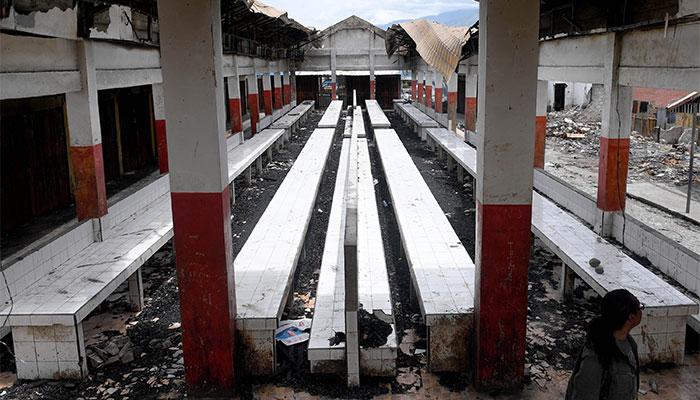 Seorang warga berada di dalam bangunan yang rusak terbakar di Pasar Wouma, Kota Wamena, Kabupaten Jayawijaya, Papua, Rabu (9/10/2019). Sejumlah bangunan kantor, rumah, toko, hingga kendaraan rusak terbakar pascaaksi unjuk rasa yang berujung anarkis pada 23 September 2019 yang menyebabkan 33 orang meninggal dunia dan 76 orang luka-luka. Antara/M Risyal Hidayat