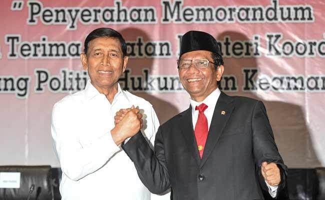 Menko Polhukam Mahfud MD (kanan) berjabat tangan dengan pejabat lama Wiranto saat serah terima jabatan di kantor Kemenko Polhukam, Jakarta, Rabu (23/10/2019). ANTARA FOTO/Hafidz Mubarak A