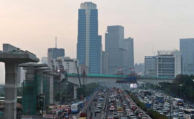 Sejumlah kendaraan bermotor melintas di Jln H.R. Rasuna Said dengan latar belakang pembangunan 'longspan' atau bentangan beton panjang lintasan Light Rail Transit (LRT) di Kuningan, Jakarta, Kamis (7/11). Menurut situs resmi LRT Jabodebek, lintasan LRT Kuningan merupakan salah satu struktur jembatan kereta api lengkung dengan struktur beton terpanjang di dunia. Sementara itu, pembangunan prasarana LRT Jabodebek sudah mencapai 66,79 persen (data terakhir Ditjen Perkeretaapian Kemenhub pada awal November 2019). ANTARA FOTO/Aditya Pradana Putra