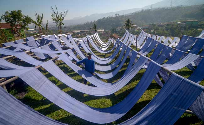 Perajin menjemur kain untuk dijadikan kain pel di sentra industri tradisional Kampung Babakan, Desa Dukuh, Kecamatan Ibun, Kabupaten Bandung, Jawa Barat, Senin (18/11/2019). Industri tenun rakyat Alat Tenun Bukan Mesin (ATBM) tersebut sudah ada sejak masa pemerintahan Hindia Belanda. Dari puluhan rumah produksi, saat ini hanya tersisa 15 rumah produksi karena minimnya regenerasi serta faktor modernisasi alat tenun. ANTARA FOTO/Raisan Al Farisi