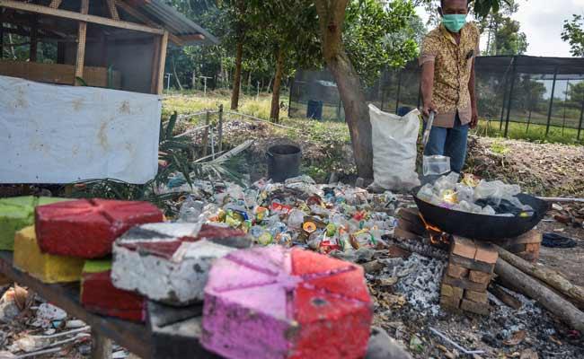 Sejumlah pengelola objek wisata Taman Bunga Impian Okura melumerkan sampah plastik untuk dijadikan paving blok di Kota Pekanbaru, Riau, Senin (19/11). Pengelola objek wisata menggunakan limbah plastik yang dihasilkan pengunjung untuk menghiasi taman bunga, dan butuh sekitar satu kilogram sampah plastik untuk pembuatan satu buah paving blok. Antara /FB Anggoro
