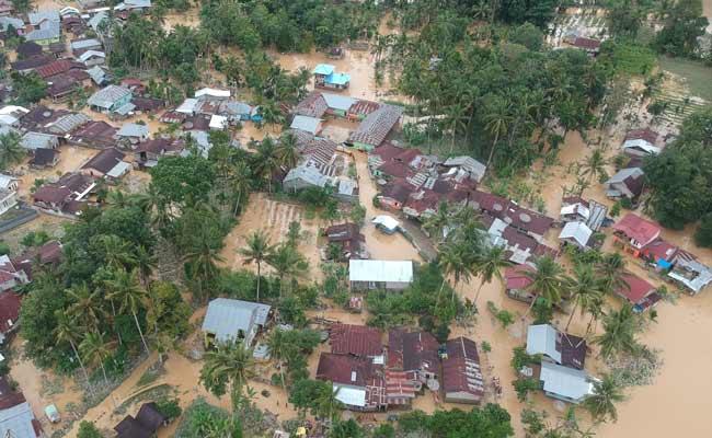 Foto udara kondisi banjir yang merendam pemukiman di Kampung Tarandam, Nagari Pasar Muara Labuah, Kab.Solok Selatan, Sumatra Barat, Jumat (13/12/2019). Data BPBD Solok Selatan menyebutkan banjir bandang mengakibatkan 1000 unit rumah terendam banjir, enam unit hanyut, satu jembatan putus dan satu orang tewas. ANTARA FOTO/Iggoy el Fitra