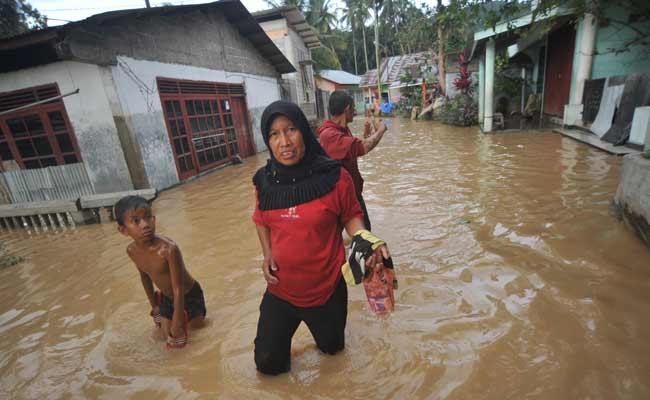 Warga melintasi banjir yang merendam pemukiman di Kampung Tarandam, Nagari Pasar Muara Labuah, Kab.Solok Selatan, Sumatera Barat, Jumat (13/12/2019). Data BPBD Solok Selatan menyebutkan banjir bandang mengakibatkan 1000 unit rumah terendam banjir, enam unit hanyut, satu jembatan putus dan satu orang tewas. ANTARA FOTO/Iggoy el Fitra