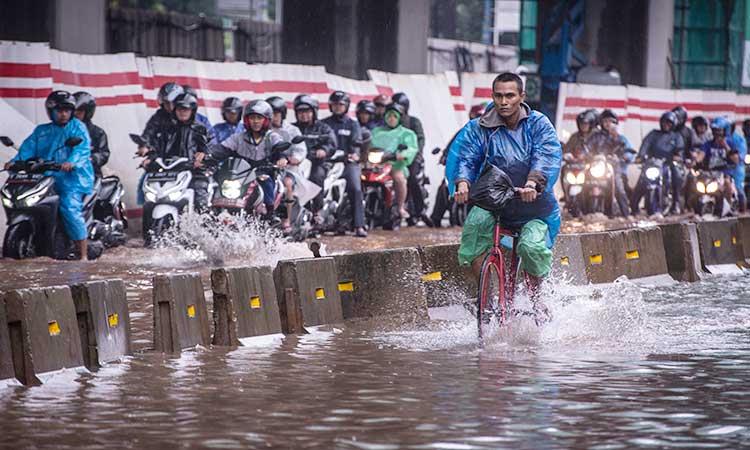 Pesepeda dan pengendara sepeda motor melintasi banjir di Jalan HR Rasuna Said, Jakarta, Selasa (25/2/2020). Banjir tersebut disebabkan karena tingginya intensitas hujan sejak Senin (24/2). ANTARA FOTO/Aprillio Akbar