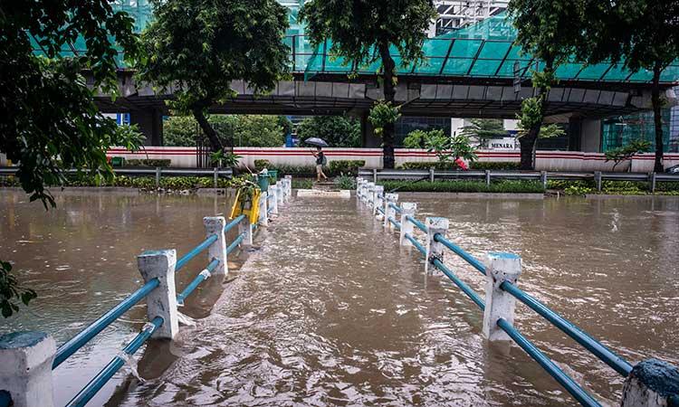 Seorang warga berjalan di dekat jembatan yang terendam luapan sungai di kawasan Jalan HR Rasuna Said, Jakarta, Selasa (25/2/2020). Banjir tersebut disebabkan karena tingginya intensitas hujan sejak Senin (24/2). ANTARA FOTO/Aprillio Akbar
