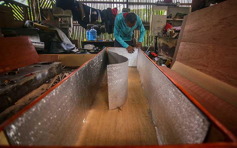 Pekerja memproduksi peti khusus jenazah COVID-19 di Jalan TMP Taruna, Kota Tangerang, Banten, Rabu (25/3/2020). Peti mati khusus jenazah COVID-19 tersebut dilapisi alumunium foil di semua sisi untuk mencegah penyebarannya dan dikirim ke rumah sakit yang menangani pasien COVID-19 di Provinsi Banten. ANTARA FOTO/Fauzan