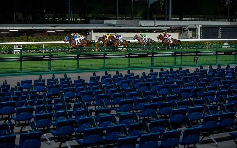 Kursi kosong terlihat saat perlombaan pavuan kuda yang tertutup bagi penonton karena virus corona di arena pacuan kuda Happy Jockey Club Hong Kong di Hong Kong, China, Rabu (25/3/2020). Hong Kong melihat kasus virus corona di luar negaranya yang melonjak sehingga memerintahkan warganya yang baru kembali dari luar negeri wajib mengikuti karantina selama 14 hari. Bloomberg/Paul Yeung