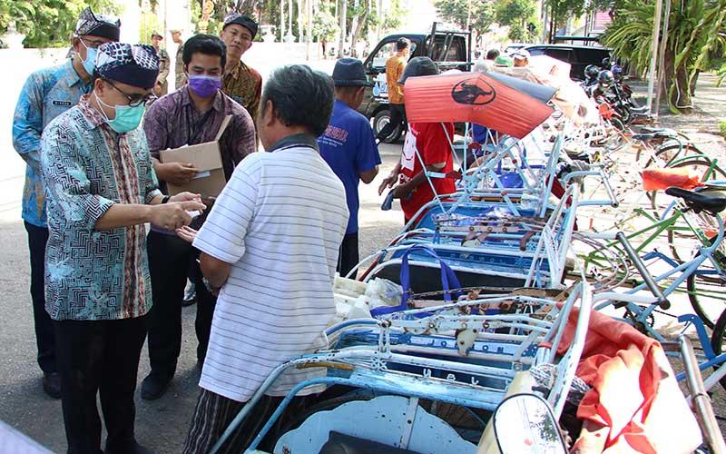 Bupati Banyuwangi Abdullah Azwar Anas (kiri) memberikan bantuan sembako kepada tukang becak di Taman Sri Tanjung, Banyuwangi, Jawa Timur, Kamis (26/3/2020). Pemberian bantuan sebagai jaring pengaman ekonomi bagi warga dengan pekerjaan mengandalkan pendapatan harian itu, seiring terus dilakukannya social distancing untuk mencegah penyebaran COVID-19. ANTARA FOTO/Budi Candra Setya