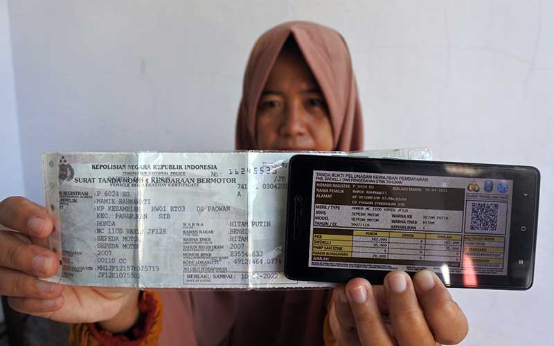 Seorang warga membayar pajak kendaraan bermotor dari rumah secara daring atau online di Panarukan, Situbondo, Jawa Timur, Kamis (26/3/2020). Pembayaran secara online itu karena diliburkannya pembayaran secara langsung melalui Samsat untuk mencegah penularan Covid-19. ANTARA FOTO/Seno