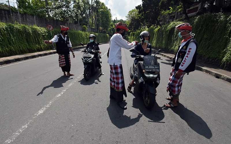 Pecalang atau petugas keamanan adat Bali memeriksa sejumlah warga yang melintas di Tabanan, Bali, Kamis (26/3/2020). Penjagaan dilakukan di setiap perbatasan desa / kota dengan melibatkan unsur pecalang, TNI dan Polri untuk mengurangi lalu lalang orang pascaimbauan gubernur Bali agar masyarakat tetap berada di rumah untuk  mencegah penyebaran COVID-19. ANTARA FOTO/Nyoman Hendra Wibowo
