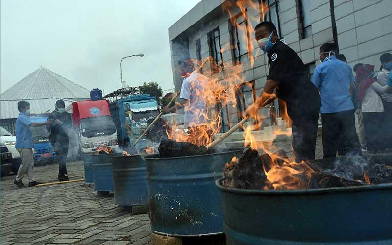 Petugas BNN (Badan Narkotika Nasional) Provinsi Banten bersama jajaran Muspida menyulut puluhan paket ganja saat Pemusnahan 50 Kilogram Ganja di Kantor BNN Provinsi Banten, di Serang, Kamis (26/3/2020). Petugas BNNP Banten menangkap kedua kurir saat akan mengambil kiriman paket 50 kilogram ganja dari Aceh yang disamarkan dalam empat keranjang asem jawa di Kantor jasa pengiriman yang setelah diusut ternyata ganja tersebut milik MF dan ND, dua warga binaan Lembaga Pemasyarakatan di Banten. ANTARA FOTO/Asep Fathulrahman