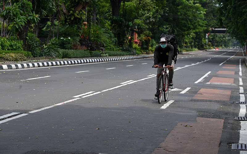 Pesepeda melintas di Jalan Darmo yang ditutup, di Surabaya, Jawa Timur, Sabtu (28/3/2020). Penutupan sejumlah jalan di Surabaya tersebut agar terbebas dari segala aktivitas warga dan kendaraan guna mencegah penyebaran Virus Corona (COVID-19). ANTARA FOTO/Zabur Karuru