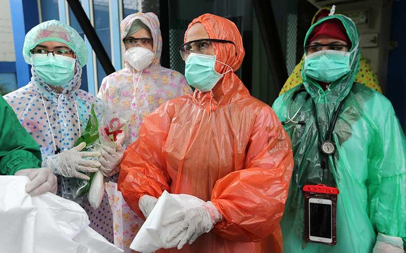 Petugas medis Puskesmas Kuta Alam memakai jas hujan plastik sebagai Alat Pelindung Diri (APD) untuk melayani pasien di Banda Aceh, Aceh, Senin (6/4/2020). Petugas medis di tingkat puskesmas terpaksa menggunakan jas hujan karena keterbatasan APD yang sesuai standar guna mencegah penularan virus Corona (COVID-19). ANTARA FOTO/Irwansyah Putra