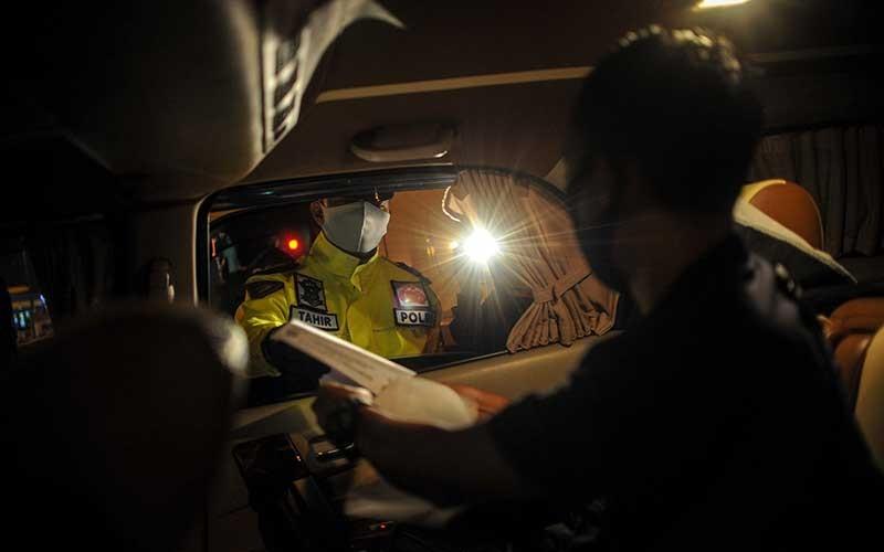 Anggota kepolisian memeriksa surat kelengkapan perjalanan di Gerbang Keluar Tol Cileunyi, Kabupaten Bandung, Jawa Barat, Jumat (22/5/2020). Pemeriksaan kendaraan yang digelar hingga H+5 Idul Fitri tersebut ditujukan untuk penyekatan masyarakat yang akan mudik menuju jalur selatan dan jalur tengah guna mencegah penyebaran COVID-19. ANTARA FOTO/Raisan Al Farisi